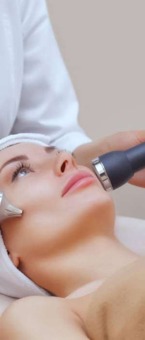 the-cosmetologist-makes-the-procedure-an-ultrasonic-cleaning-of-the-facial-skin-of-a-beautiful-young-woman-in-a-beauty-salon